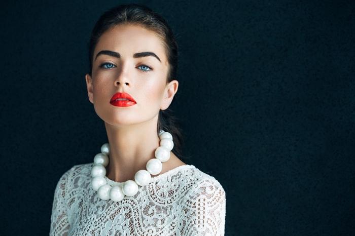 trucco novità con le labbra rosse, gli occhi blu truccati con un ombretto color carne, una grande collana di perle bianche
