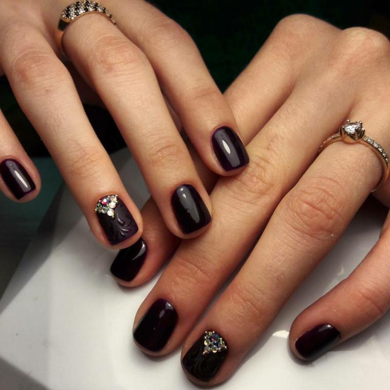 Unghie nere opache sul dito anulare, decorazione con brillantini, smalto nero lucido sul resto delle dita