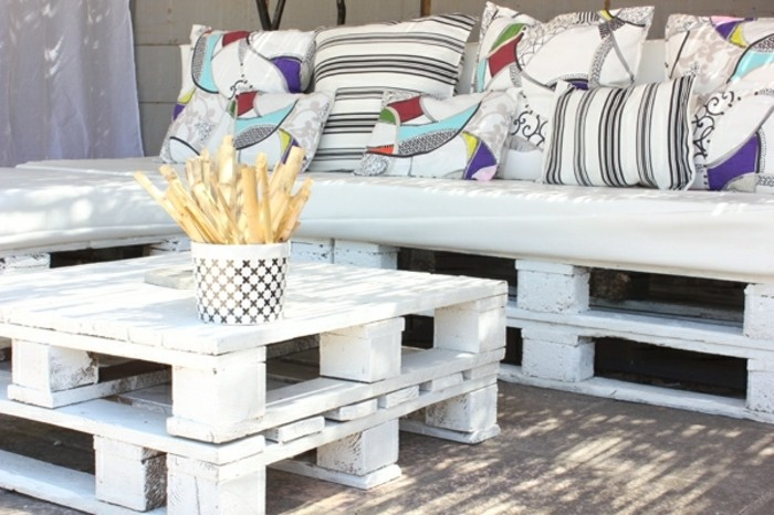 Idea divano pallet da esterno. dipinto con vernice di colore bianco, tavolino basso con due bancali