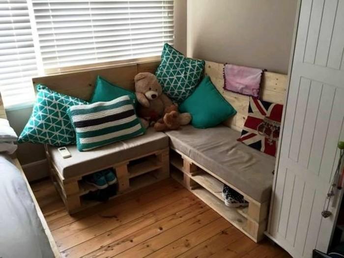 Idea arredamento con bancali, divano ad angolo decorato con cuscini colorati