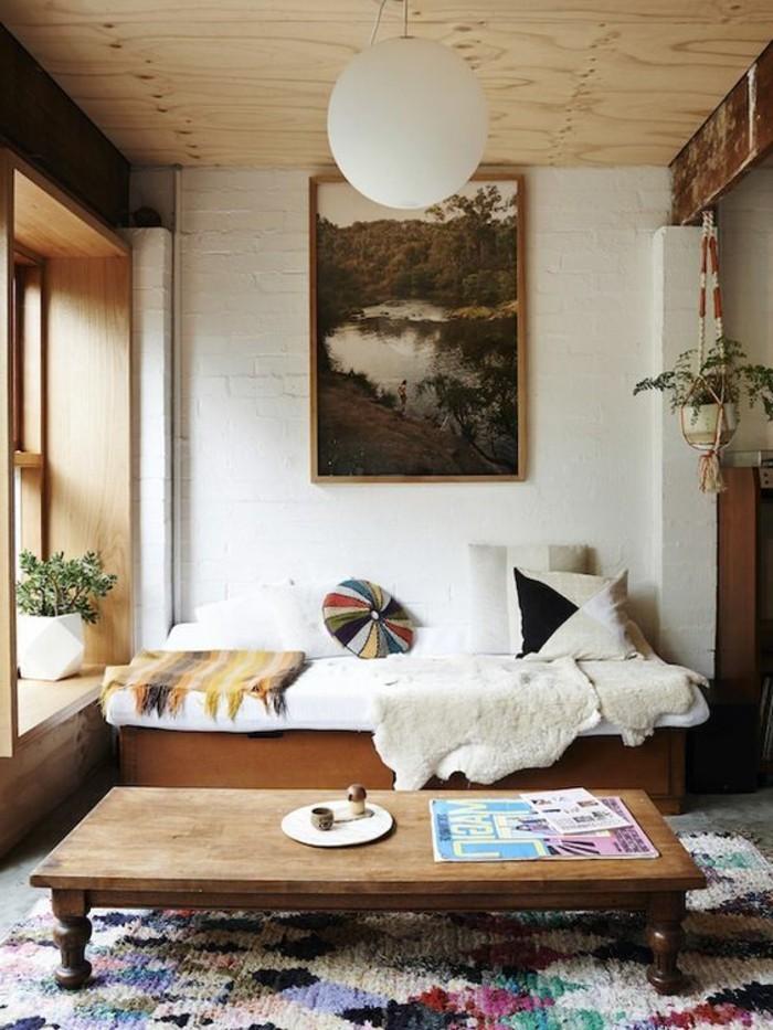 Arredare salotto piccolo con un divano letto in legno e un tavolino basso, decorazione con un tappeto colorato stile etnico