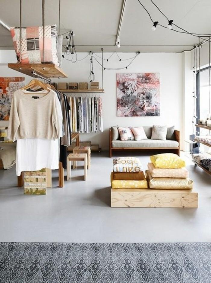 Arredamento monolocale con zona giorno e zona notte, divano letto in legno con cuscineria di colore grigio