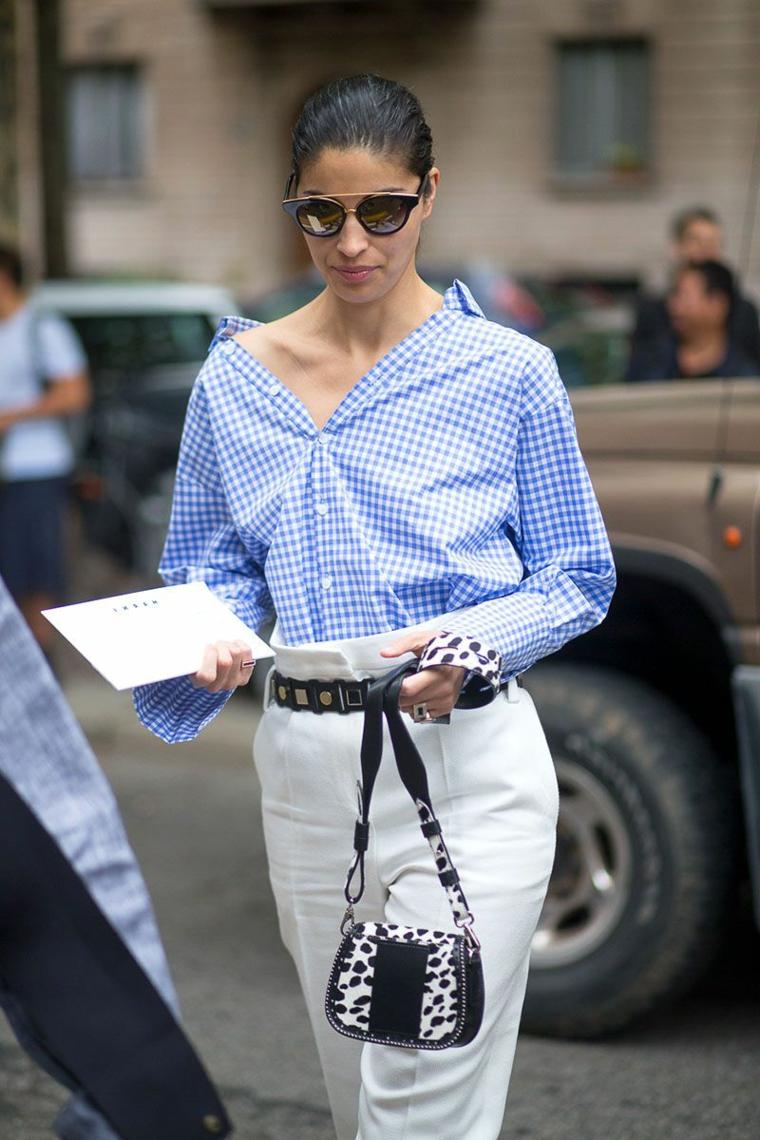 Pantalone bianco con taglia alta e cintura, camicia blu a quadretti e borsetta piccola