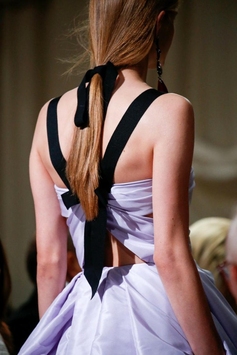 una ragazza con i capelli lunghi e lisci raccolti in una coda con un nastro nero