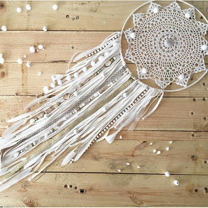 un modello tutto bianco di dream catcher con una stoffa decorata all'interno del cerchio e delle perline