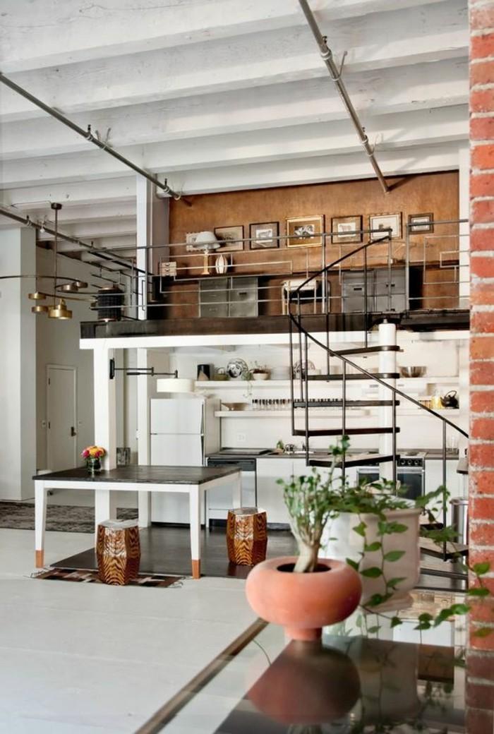 Soppalco in un monolocale decorato con parete in legno e tanti quadri