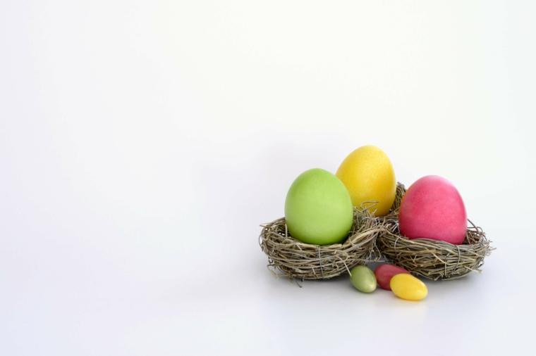 un esempio di immagini di uova di pasqua verdi, gialli e rosa all'interno di piccoli nidi