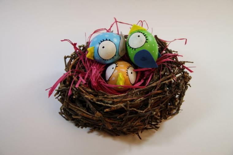 un esempio di addobbi pasquali con un nido e delle uova trasformate in pulcini con grandi occhi, becco e ali