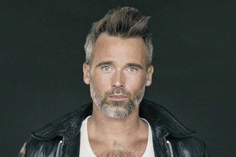 un esempio di taglio di capelli uomo over 40 alla moda, occhi azzurri e giacca di pelle