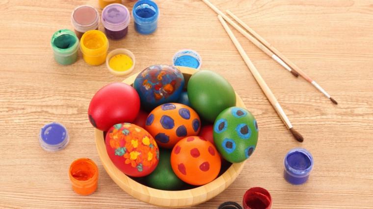 Uova dipinte con dei colori a tempera, tavolo di legno e pennelli con cui dipingere