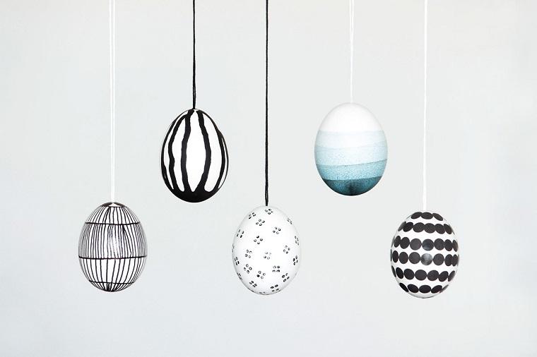 Uova colorate e decorate con forme geometriche e appese a dei fili