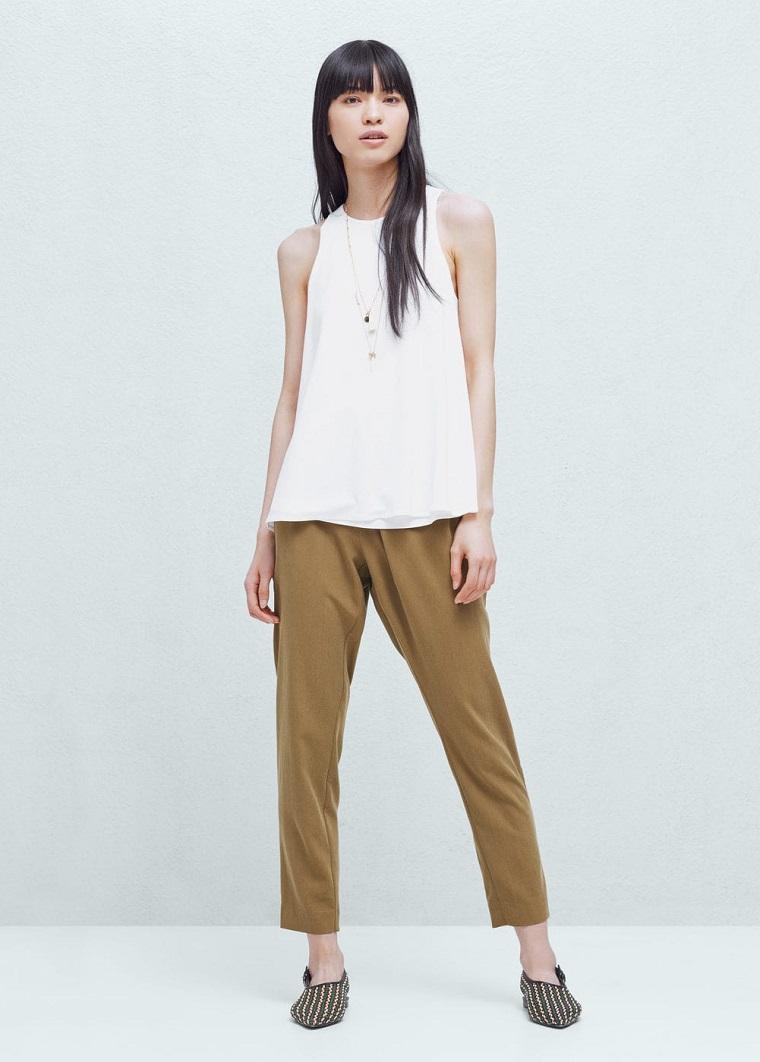 Combinare un top bianco elegante con pantaloni laghi di colore marrone