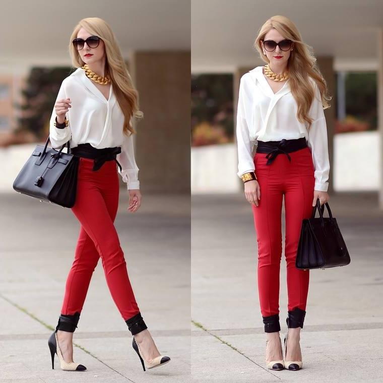 Donna con i capelli biondi, pantalone rosso stretto abbinato ad una camicia bianco con decoltè V