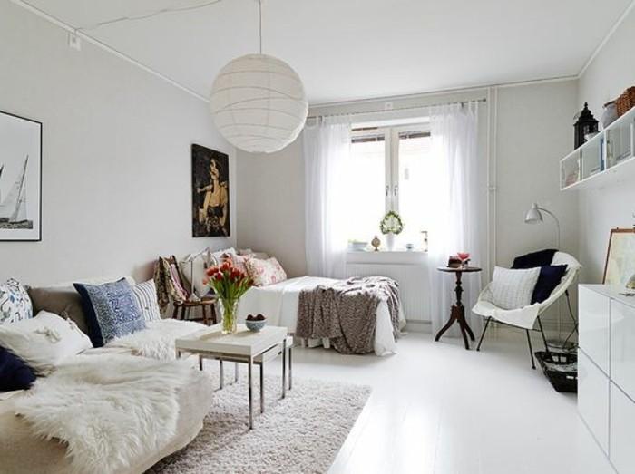 Camera da letto con un piccolo soggiorno, divano e tavolino basso, decorazioni con fiori e quadri