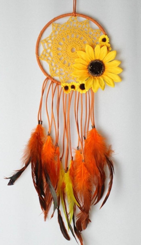 un modello di cream catcher con l'interno del cerchio giallo con un girasole e delle piume decorative arancioni