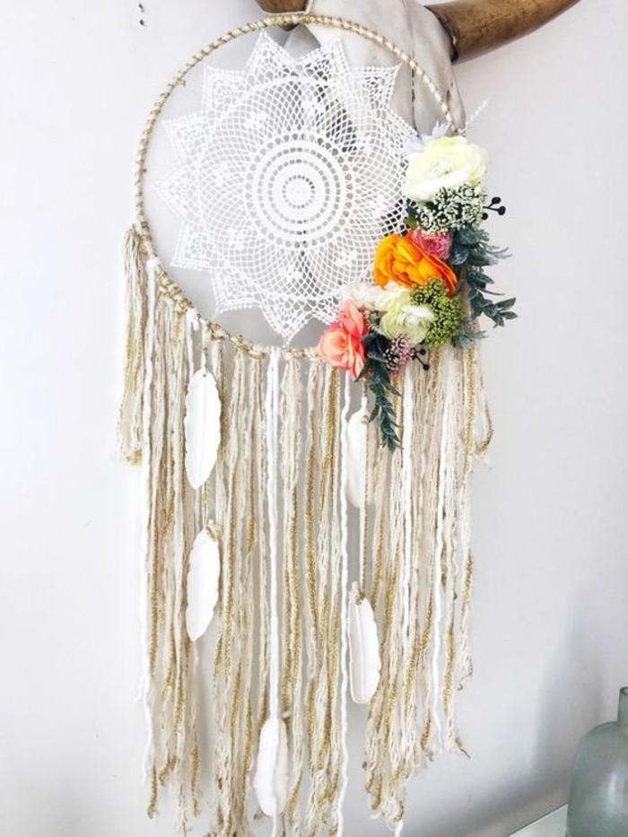 un dream catcher realizzato con della stoffa in pizzo bianco, fiori e piume