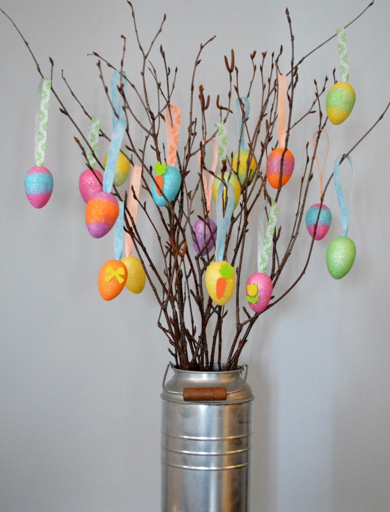 un vaso di latta con manico in legno con all'interno dei rami e degli addobbi pasquali fai da te a forma di uovo