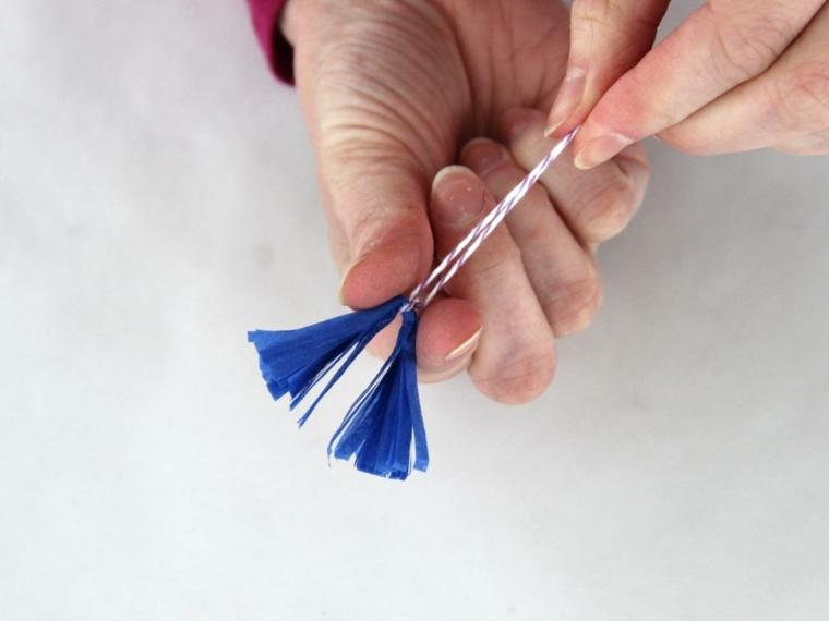 tutorial per come creare delle decorazioni pasquali fai da te: inserire il cordoncino nella carta crespa piegata e tagliata