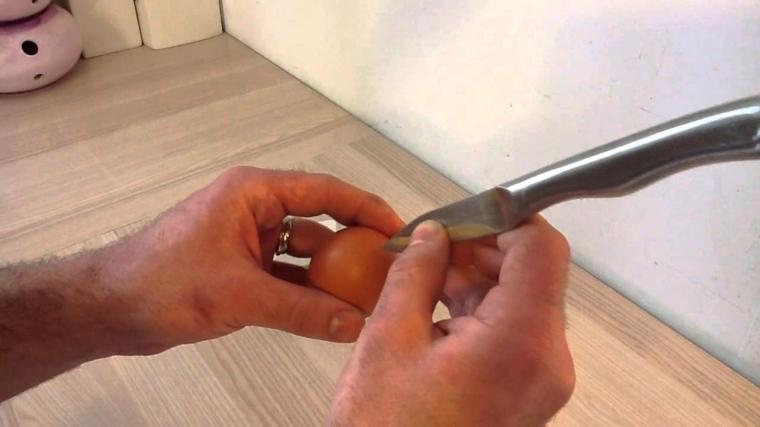 un coltello appuntito con il quale si praticano due fori per svuotare l'uovo, mani di un uomo