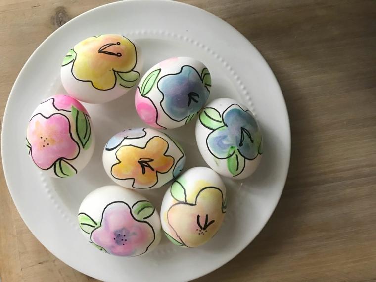 un'idea per delle uova di pasqua da colorare con dei fiori azzurri, gialli, viola e rosa su un piatto bianco