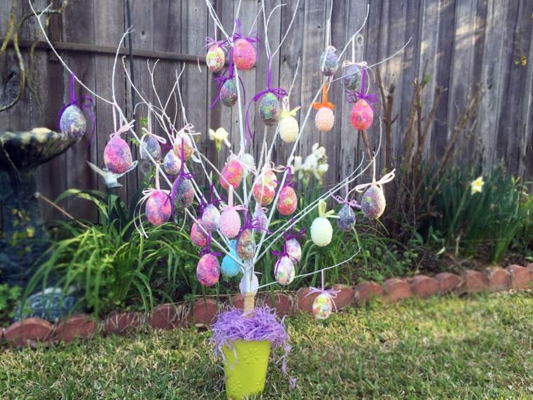 un piccolo albero in un vaso verde decorato con tante uova di pasqua colorate