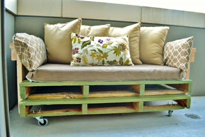 Arredamento con un divano in pallet, morbida cuscineria, bancale di legno dipinto di verde