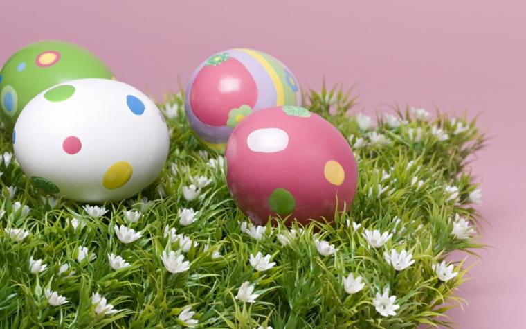 delle piccole margherite bianche su un prato con delle uova pasqua bianche, rosa con pois colorati
