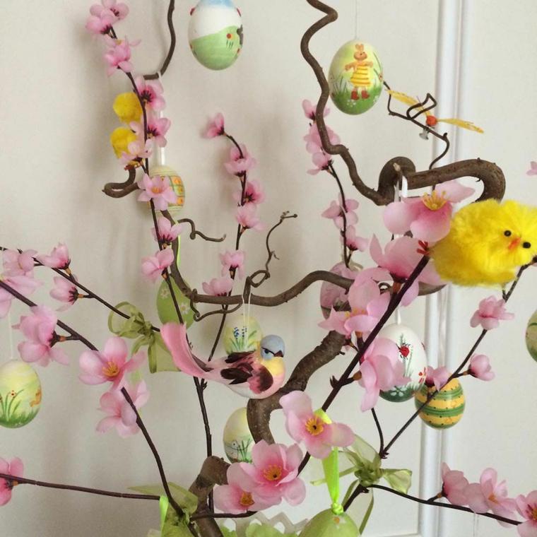 un esempio di decorazioni pasquali fai da te con dei rami di mandorlo fioriti, dei pulcini e delle uova decorate