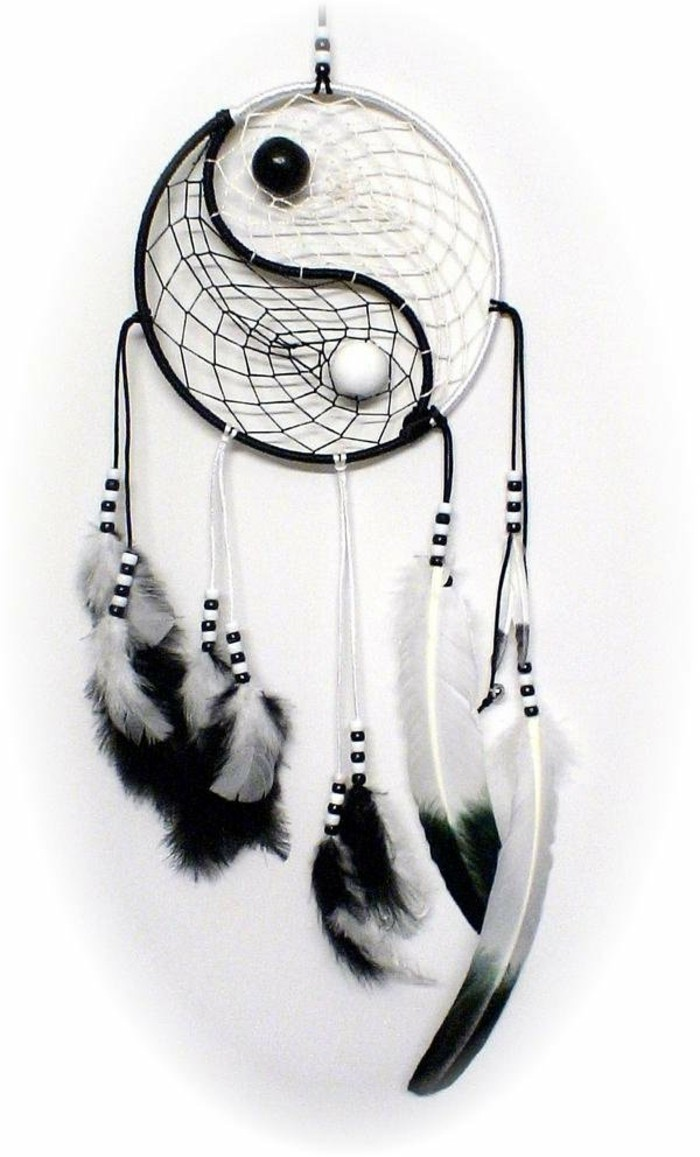 un modello di cattura sogni legato al simbolo del tao, decorazioni con piume bianche e nere