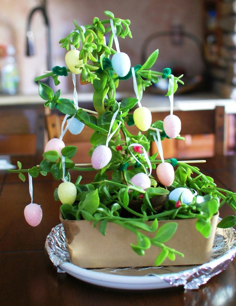 una pianta grassa con vaso rettangolare addobbata con delle uova di pasqua colorate