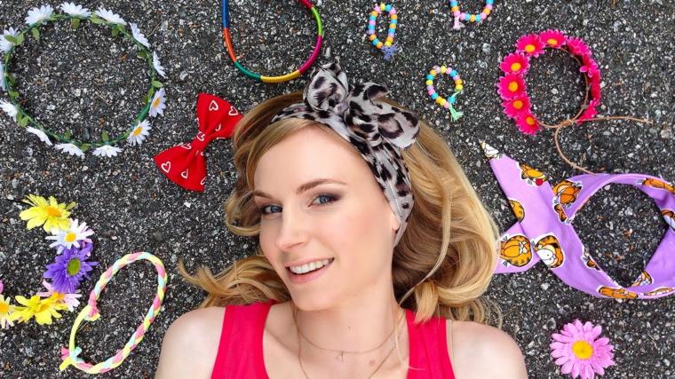 una ragazza sorridente con i capelli raccolti morbidi con una fascia in tessuto con fiocco maculata