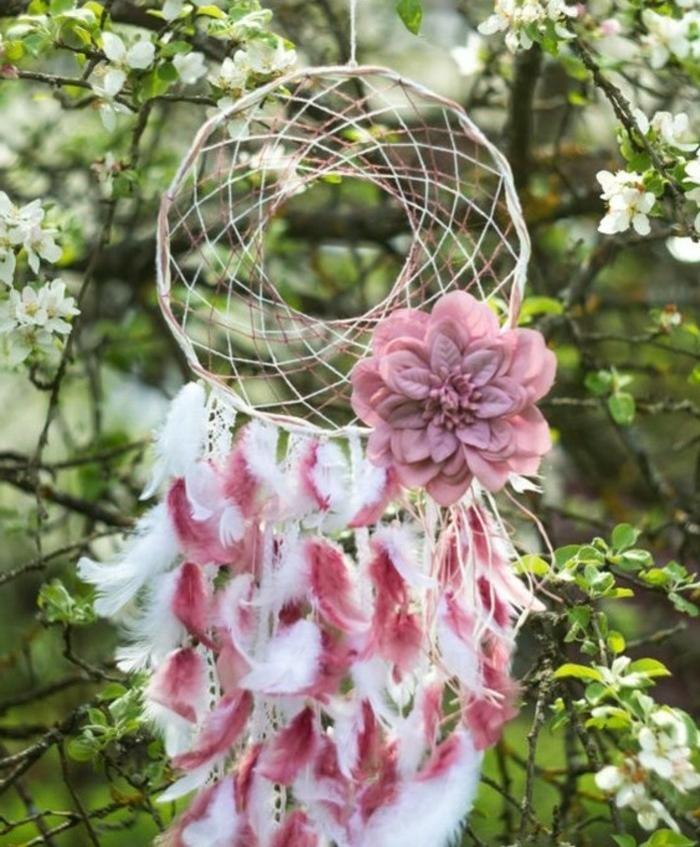 un'idea per come costruire un acchiappasogni decorandolo con piume bianche e rosa e un grande fiore