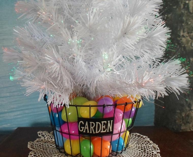 idea creativa per una decorazione pasquale, un cestino con uova colorate e piume bianche