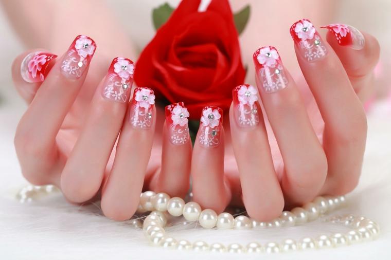 un'idea per realizzare delle unghie french con lo smalto rosso e delle decorazioni a forma di fiore