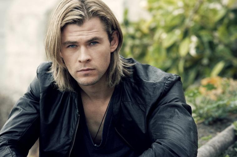 un ragazzo con i capelli lunghi biondi e lisci, una giacca e una camicia nere