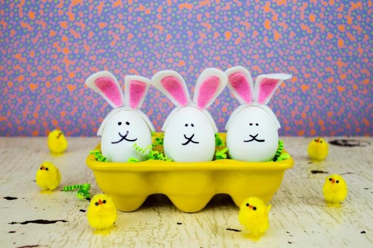 una scatola per le uova gialla con all'interno delle uova pasqua con grandi orecchie da coniglio rosa