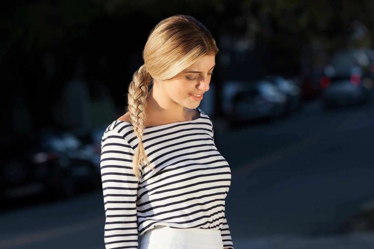 una pettinatura semplice e alla moda con una treccia a lato, maglia in stile marinaro