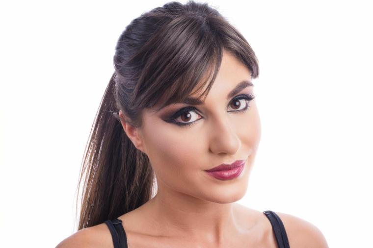 una modella con i capelli lunghi e castani con la frangia, rossetto scuro e matita nera