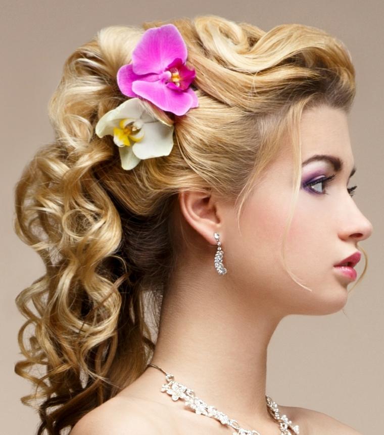 una sposa con i capelli raccolti morbidi e ondulato, due orchidee a lato, orecchini di brillanti pendenti