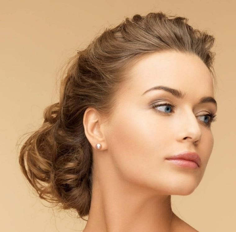un esempio di capelli legati in uno chignon basso e morbido, orecchini a perla e rossetto rosato