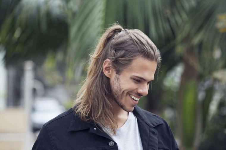 una proposta di taglio capelli maschili lunghi con un semi raccolto e una treccia, giacca scura e t-shirt chiara