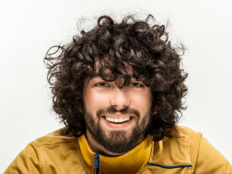 un esempio di taglio maschile per capelli ricci, barba e giacca color senape con cerniera blu