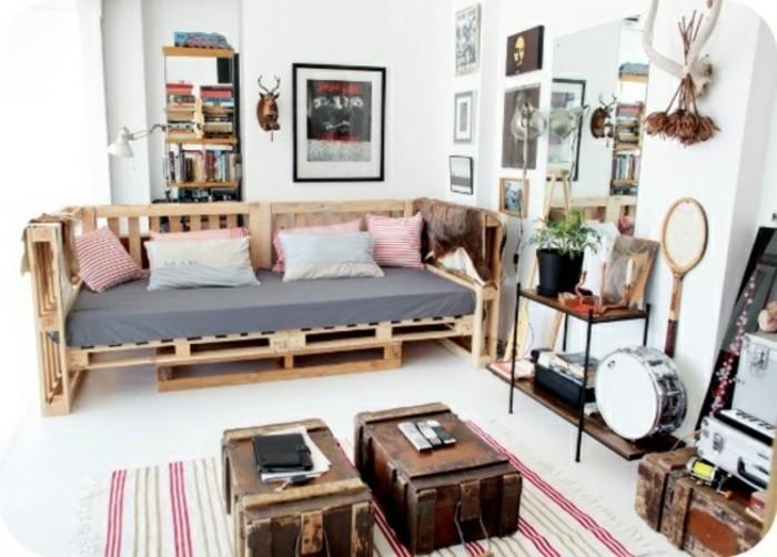 Ambiente arredato con divano in pallet, valigie vintage utilizzate come tavolini