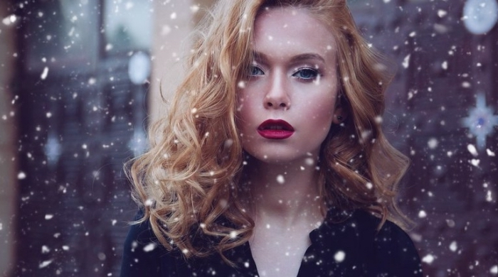 una ragazza con i capelli ramati mossi, le labbra carnose con del rossetto scuro
