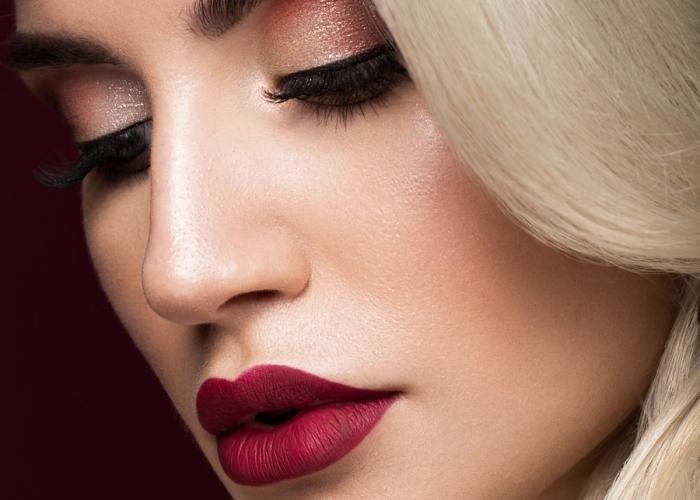 una ragazza bionda con labbra carnose e del rossetto bordeaux, ombretto marrone perlato e capelli biondi