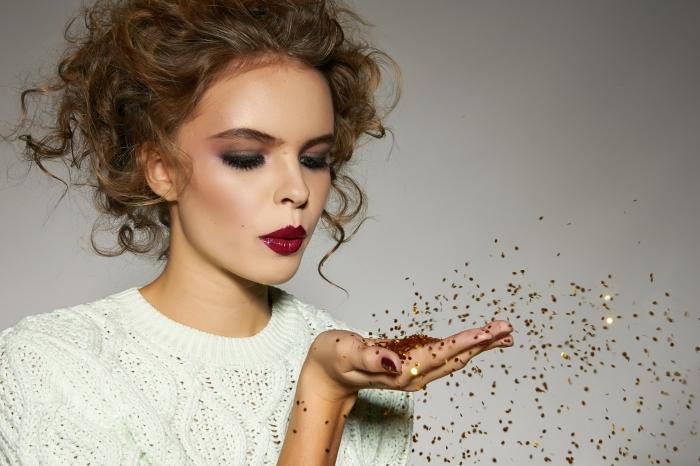 una ragazza con un maglione bianco, i capelli ricci raccolti e del rossetto bordeaux