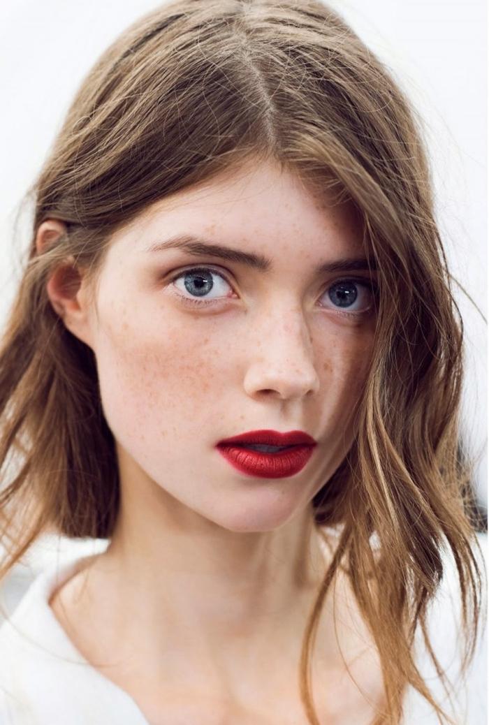 labbra truccate con del rossetto rosso scuro, capelli lunghi con la riga in mezzo
