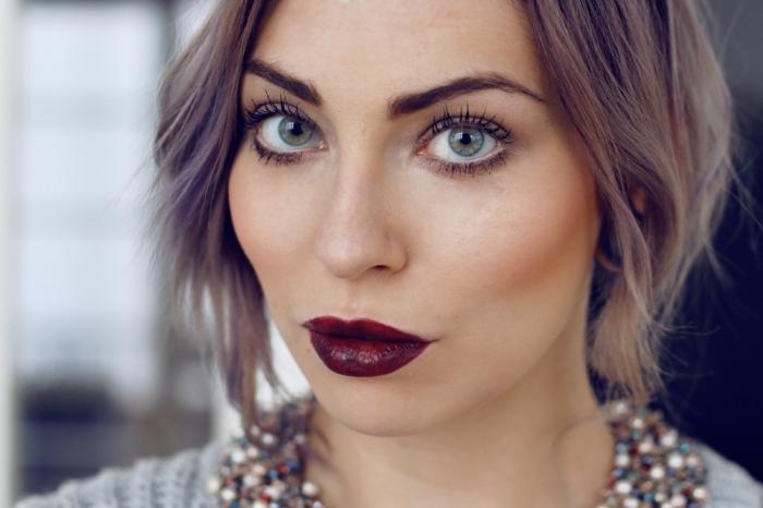 una ragazza con i capelli corti, un rossetto bordeaux scuro e gli occhi verdi truccati con una matita nera
