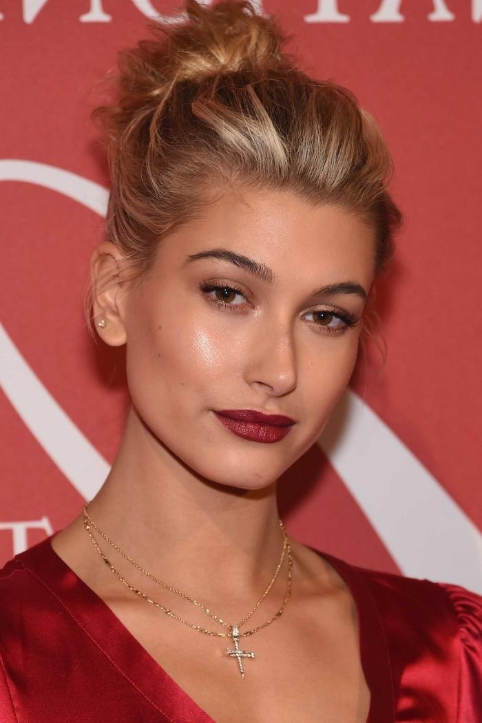 labbra truccate con un rossetto scuro, capelli biondi raccolti in uno chignon alto