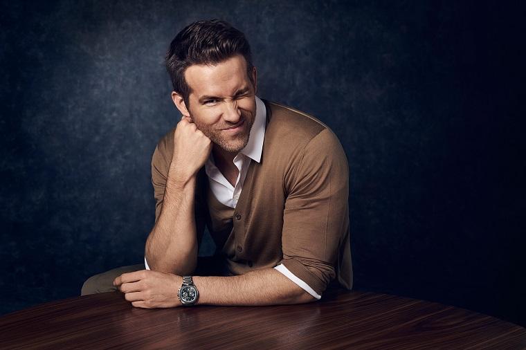 L'attore Ryan Reynolds fa l'occhiolino, appoggiato su un tavolo di legno
